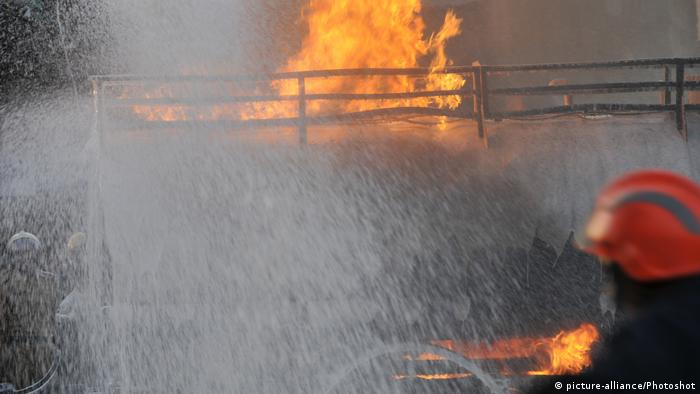 Firefighter sprays water on a burning tanker in Bangladesh