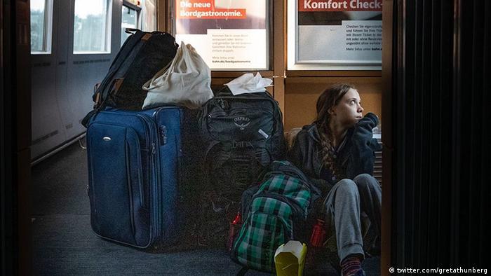 Greta Thunberg sits on the floor of a German train