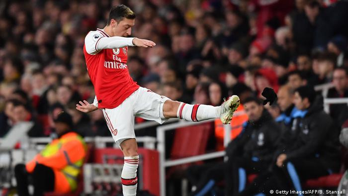 Mesut Özil kicks his gloves after being substituted during the Arsenal vs Manchester City game