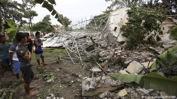 People looking at earthquake damage (picture-alliance/AP Photo)