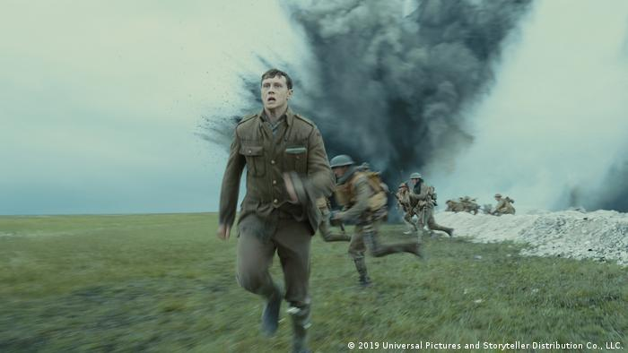 Still from '!917': soldiers in field flee an explosion (2019 Universal Pictures and Storyteller Distribution Co., LLC.)