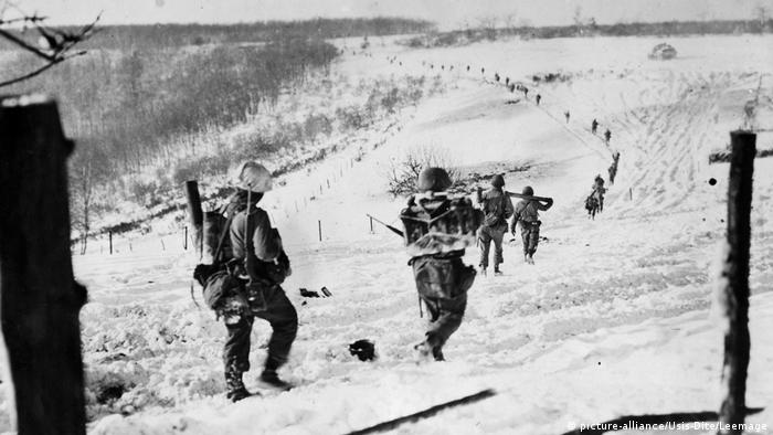 Allied soldiers carry munitions during the Battle of the Bulge