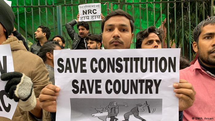 A man in India holds a sign reading Save constitution save country
