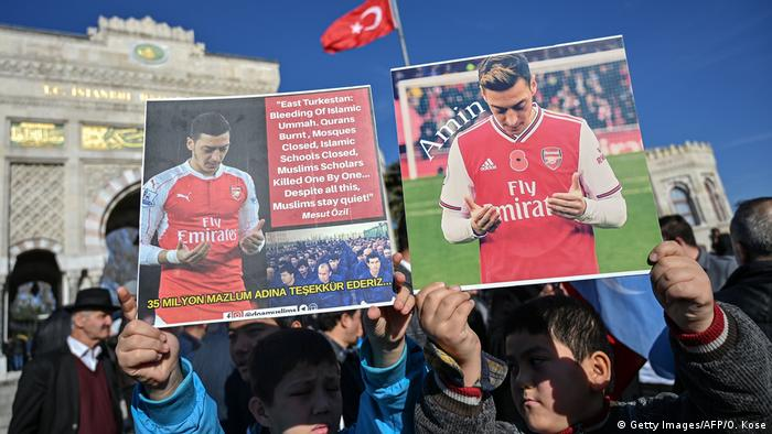 Supporters of China's Muslim Uighur minority hold placards of Arsenal's Turkish origin German midfielder Mesut Ozil