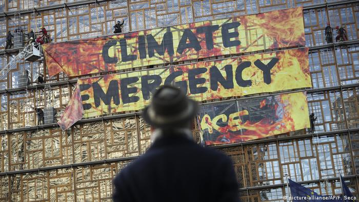 A Greenpeace banner reads Climate Emergency