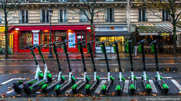 A row of e-scooters on a road