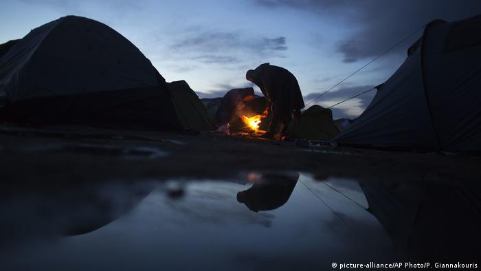 Two refugees warm up over a makeshift fire after a rainfall, while waiting to be allowed to cross the border into North Macedonia at the northern Greek border station of Idomeni