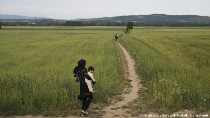 A woman walks through a field with her baby as a group of refugees and migrants leave the northern Greek border station of Idomeni