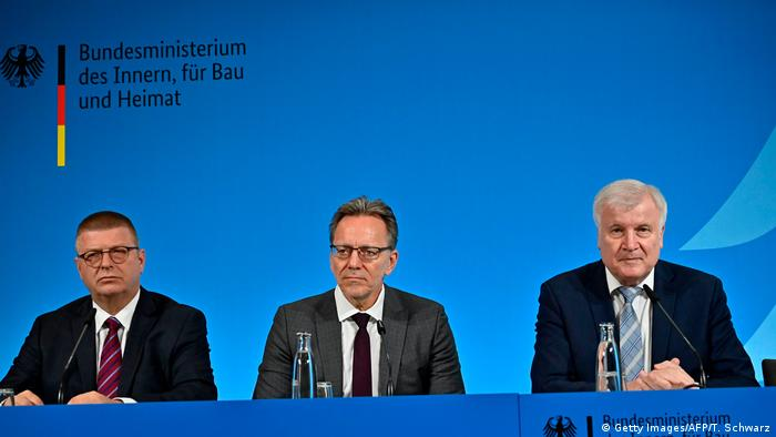 Haldenwang, Münch and Seehofer sit at a table while announcing new intelligence measures against right-wing extremism