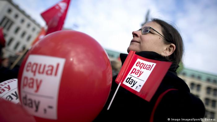 A protester carrying Equal Pay Day flags and balloons in Berlin at an Equal Pay Day demonstration on March 18, 2019
