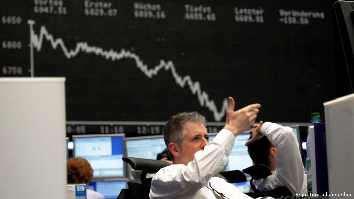 Traders work as the DAX index curve is displayed on a large screen in Frankfurt, Germany