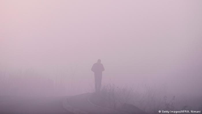 A lone figure shrouded in visible smog