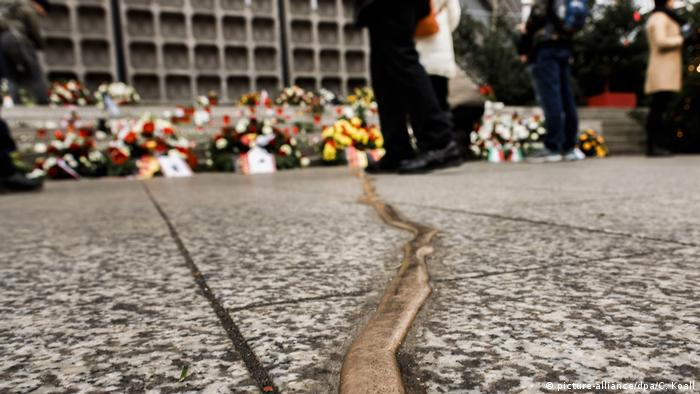 Passers-by stand at the Christmas market at Breitscheidplatz next to the memorial Goldener Riss (Golden Crack) for the victims of the terror attack on December 19, 2016. (picture-alliance/dpa/C. Koall)