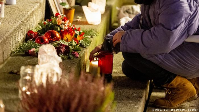 A woman lights a candle at the Christmas market at Breitscheidplatz at the memorial for the victims of the assassination on December 19, 2016.