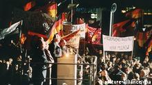 Bundeskanzler Helmut Kohl (Rednerpult, M) spricht am Abend des 19. Dezember 1989 zu der riesigen Menschenmenge, die sich anlässlich seines Besuches eingefunden hat. Rechts neben Kohl Bundesarbeitsminister Norbert Blüm. Auf Plakaten wird der Ruf nach einer Wiederveinigung laut. Kohl hielt sich zu einem zweitägigen Besuch in der sächsischen Stadt auf und wurde an beiden Tagen von der DDR-Bevölkerung stürmisch gefeiert. |