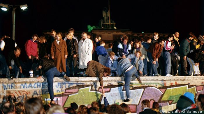 People climbing the Berlin Wall on November 9, 1989. (picture-alliance/akg-images)