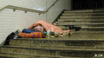 A homeless man sleeps in a stairwell in Berlin