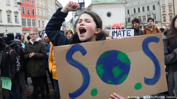 Menina com cartaz S.O.S, com desenho da Terra como O, durante manifestação