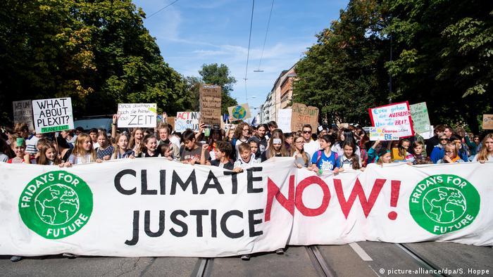 Demonstranten marschieren hinter einem Banner mit der Aufschrift Climate Justice Now