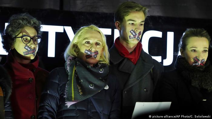 Demonstranten mit zugeklebten Mündern (Foto: Picture Alliance)