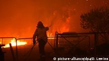 19.12.2019, Australien, Tahmoor: Feuerwehrleute versuchen südwestlich von Sydney einen Buschbrand zu löschen. Aufgrund der verheerenden Buschbrände ist in Australiens bevölkerungsreichstem Bundesstaat New South Wales erneut der Notstand ausgerufen worden. Foto: Dean Lewins/AAP/dpa +++ dpa-Bildfunk +++  