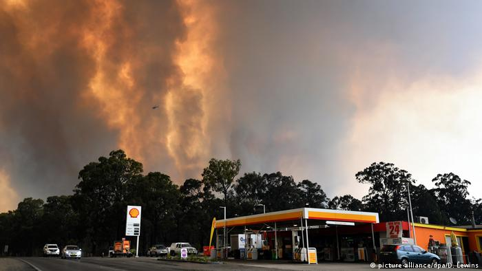 Flames several meters high loom over a Shell gas station