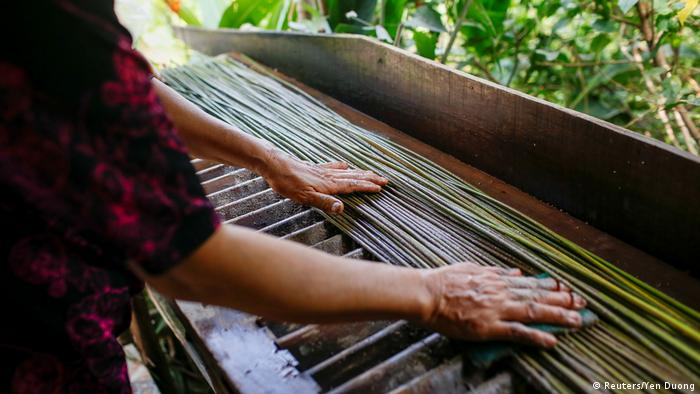 A worker washes the long stems of grass (Reuters/Yen Duong)