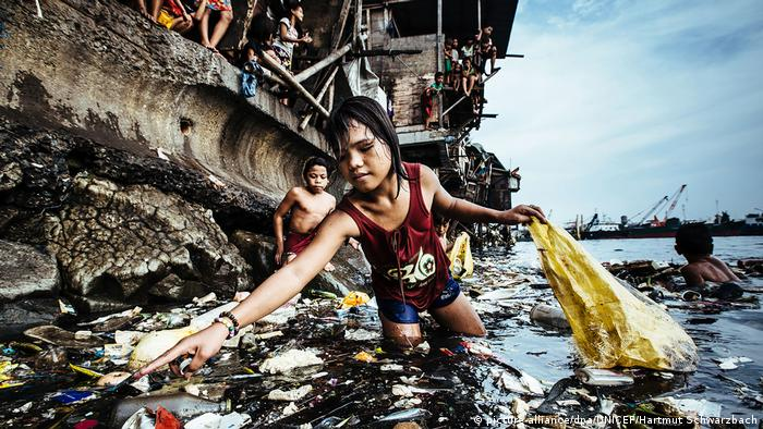 Young girl collects plastic waste in a port in Manila