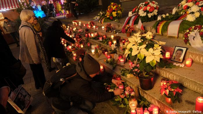 People lay flowers at the memorial to the 2016 Breitscheidplatz Christmas market attack in Berlin