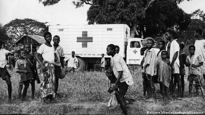 Residents in Biafra line up outside a red cross aid truck in 1970
