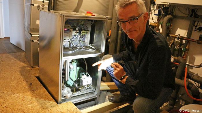 Passivhausexperte Andreas Nordhoff zeigt auf eine Wärmepumpe. Sie ist nicht größer als ein Kühlschrank. Sie nutzt die Wärme aus dem Boden. Hier heizt sie ein Haus mit 490 Quadratmeter in Köln (Warmwasser und Heizung) und braucht rund 3500 kWh Strom. Die PV-Anlage auf dem Dach liefert pro Jahr rund 12.000 kWh Strom. So wird mit dem Haus mehr Energie erzeugt als jährlich verbraucht wird.