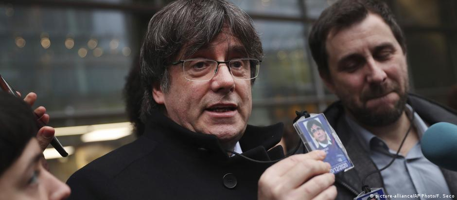 Catalonia's former regional president Carles Puigdemont, center, shows his badge to journalists as he stands next to former Catalan regional minister Antoni Comin outside the European Parliment in Brussels