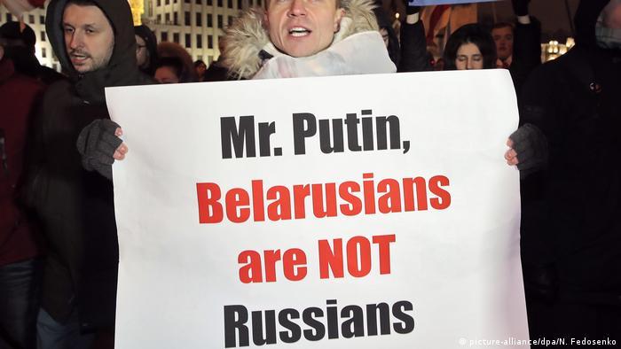 Участник акции стоит с плакатом: Мистер Путин, белорусы - не россияне