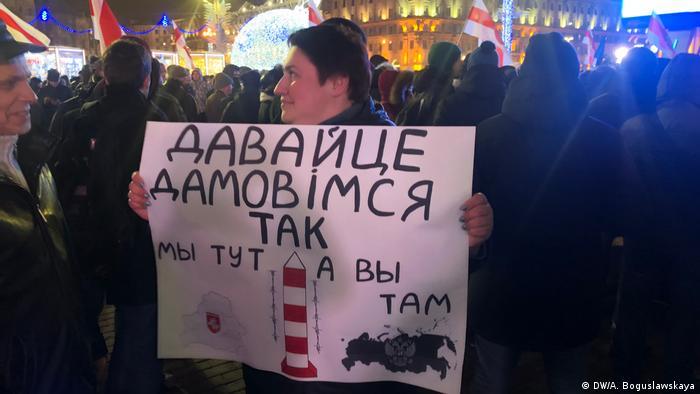 Участница акции протеста в Минске держит плакат с надписью: Давайте договоримся так: мы - тут, а вы - там
