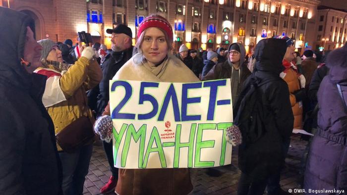 Участница акции протеста держит плакат: 25 лет - ума нет