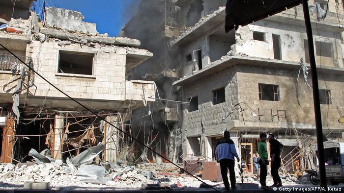 Люди стоят у разрушенного здания в провинции Идлиб в Сирии