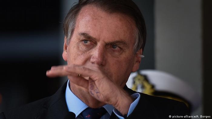 Jair Bolsonaro gesticula com a mão esquerda