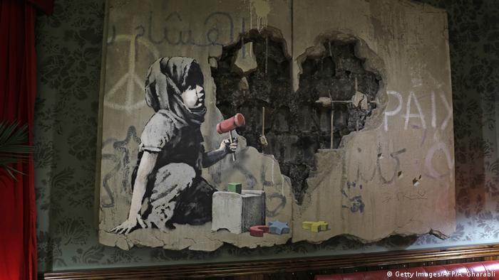 Grafiti de uma criança brincando, com um buraco em forma de coração num muro