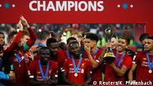 Soccer Football - Club World Cup - Final - Liverpool v Flamengo - Khalifa International Stadium, Doha, Qatar - December 21, 2019 Liverpool's Roberto Firmino celebrates with the trophy and teammates after winning the Club World Cup REUTERS/Kai Pfaffenbach