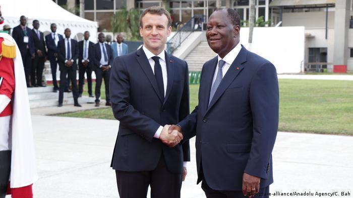 French President Emmanuel Macron and Ivory Coast President Alassane Ouattara shake hands