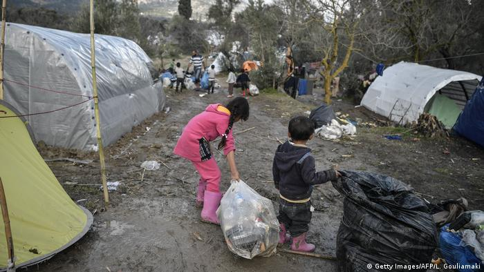 Children help clear up rubbish at a migrant camp after a heavy bout of rain on the island of Chios in December