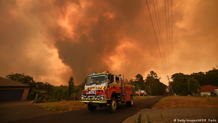 Firetrucks are seen stationed on a road as a bushfire burns