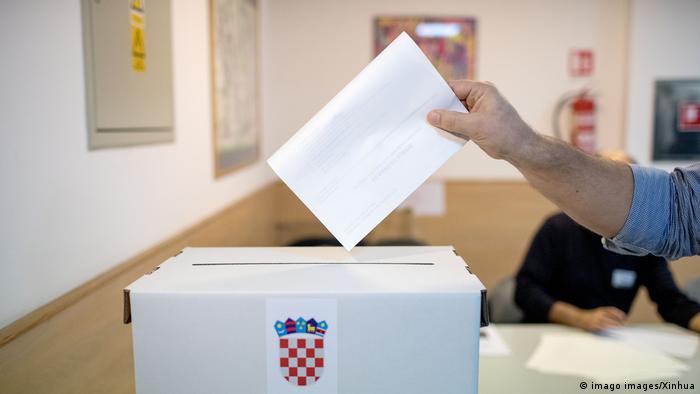 Osoba ubacuje izborni listić u kutiju