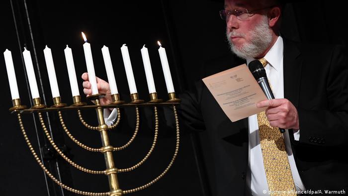 Rabbi Schmuel Aharon Brodman lights a menorah in Munich for the start of Chanukah and International Holocaust Survivors Night. (dpa)