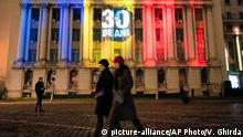 People walk outside the former building of the communist party central committee, the place where Nicolae Ceausescu delivered his last speech 30 years ago today, during an event commemorating those killed in the 1989 anti-communist uprising in Bucharest, Romania, Sunday, Dec. 22, 2019. Romania marks the 30th anniversary of the anti-communist uprising which started in the western Romanian town of Timisoara on Dec. 16 and in Bucharest on Dec. 21, 1989, left more than one thousand people dead and ended the rule of dictator Nicolae Ceausescu. (AP Photo/Vadim Ghirda)