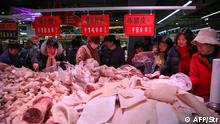 This photo taken on December 19, 2019 shows people trying to buy meat at a newly-opened supermarket in Binzhou, in China's eastern Shandong Province. - The supermarket offered 3 tonnes of pork at discounted prices as a promotion. Pork prices in China have doubled this year following an outbreak of African swine fever. (Photo by STR / AFP) / China OUT