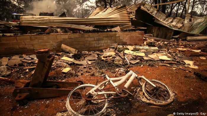 A burnt bicycle lies on the ground in front of a house destroyed by bushfires (Getty Images/D. Gay)