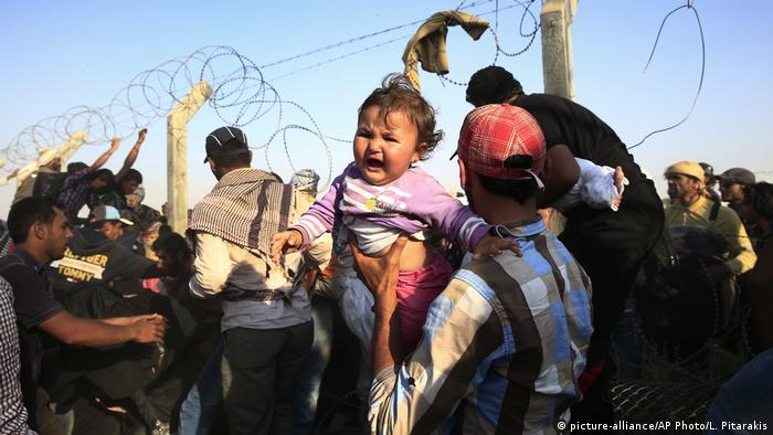 A Syrian refugee carries a baby after crossing over the broken border fence into Turkey from Syria in Akcakale, Sanliurfa province, southeastern Turkey
