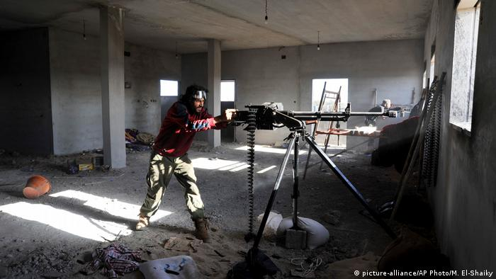 In this picture taken Thursday, March 10, 2016, fighters against the Islamic State group fire weapons in the Hawari area, south-west of the city of Benghazi, Libya