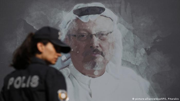 Сотрудница полиции на фоне плаката с изображением Джамаля Хашогги